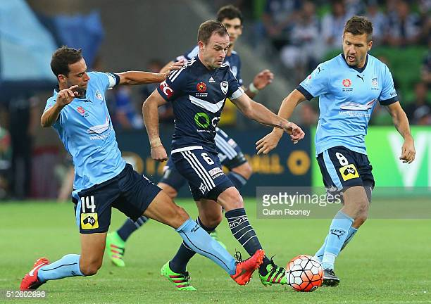 Leigh Broxham of the Victory is tackled by Alex Brosque of Sydney FC during the round 21 ALeague match between Melbourne Victory and Sydney FC at...
