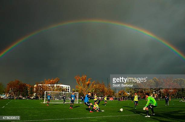 Leigh Broxham of the Victory makes a sliding tackle as a rainbow forms overhead during a Melbourne Victory ALeague training session at Gosch's...