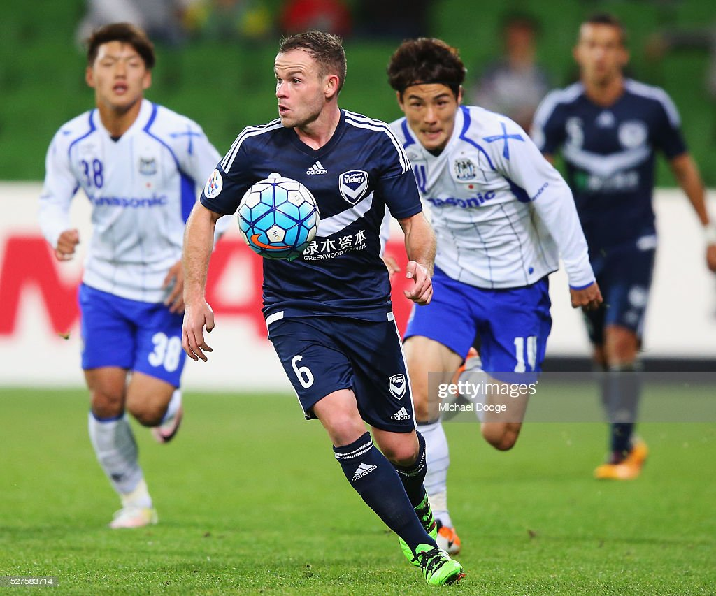 Leigh Broxham of the Victory runs with the ball ahead of Koki Yonehura of Gamba Osaka during the AFC Champions League match between Melbourne Victory and Gamba Osaka at AAMI Park on May 3, 2016 in Melbourne, Australia.