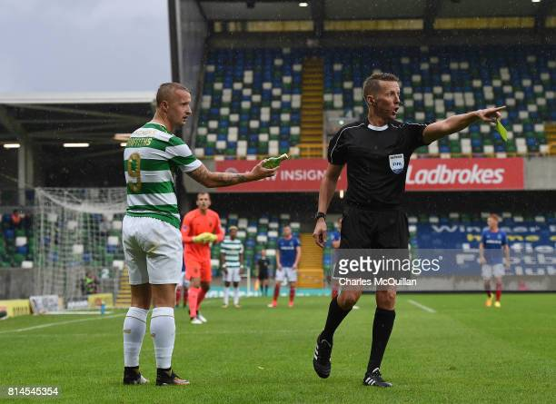 Leigh Griffiths of Celtic holds up one of the bottles thrown at him by Linfield fans towards the referee Konrad Plautz who then booked Griffiths for...