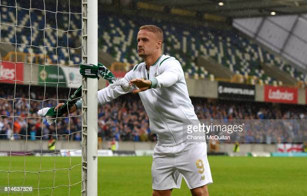 Leigh Griffiths of Celtic ties a Celtic scarf around the goal post after the Champions League second round first leg qualifying game between Linfield...