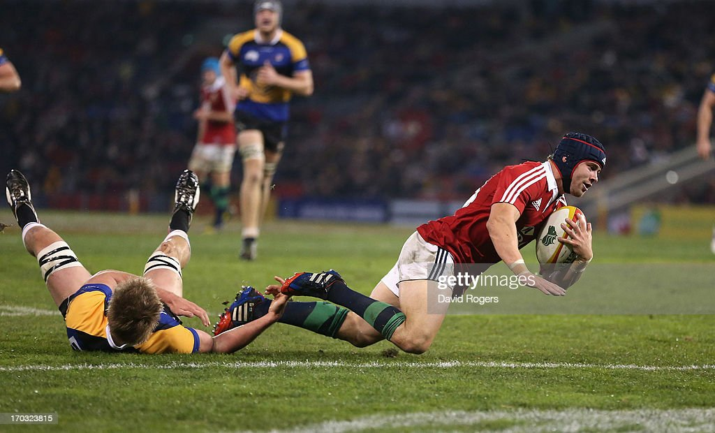 Leigh Halfpenny of the Lions breaks away from Trent Dyer to score a try during the match between Combined Country and the British & Irish Lions at Hunter Stadium on June 11, 2013 in Newcastle, Australia.