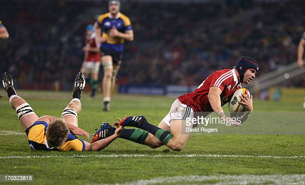 Leigh Halfpenny of the Lions breaks away from Trent Dyer to score a try during the match between Combined Country and the British Irish Lions at...