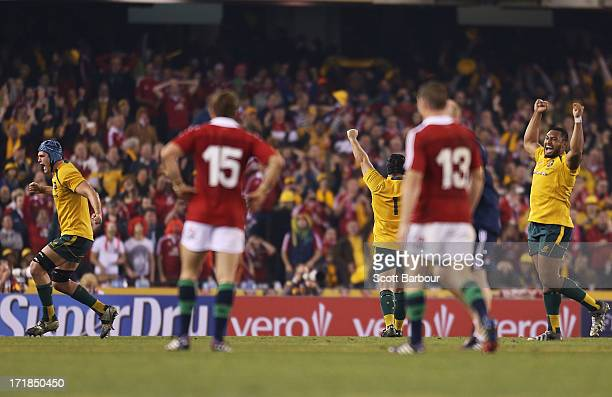 Leigh Halfpenny of the Lions looks on after missing a penalty kick in the final minute as James Horwill and Benn Robinson celebrate victory during...