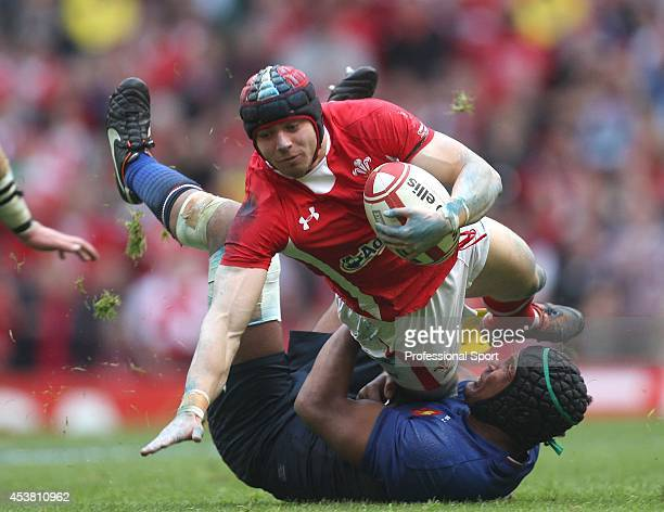 Leigh Halfpenny of Wales is brought down by Thierry Dusautoir of France during the RBS Six Nations Championship match between Wales and France at the...