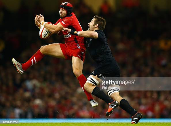 Leigh Halfpenny of Wales is tackled by Richie McCaw during the Intenational match between Wales and the New Zealand All Blacks at the Millennium...
