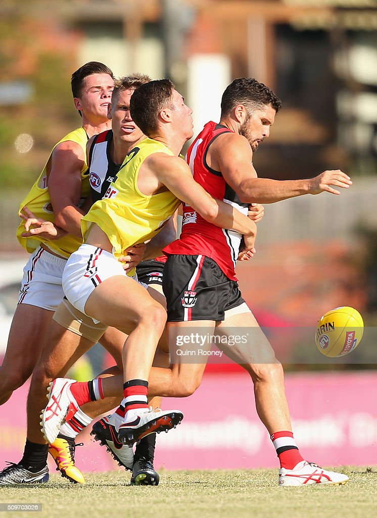 Leigh Montagna of the Saints kicks whilst being tackled by Jade Gresham during the St Kilda Saints AFL Intra-Club Match at Trevor Barker Beach Oval on February 12, 2016 in Melbourne, Australia.
