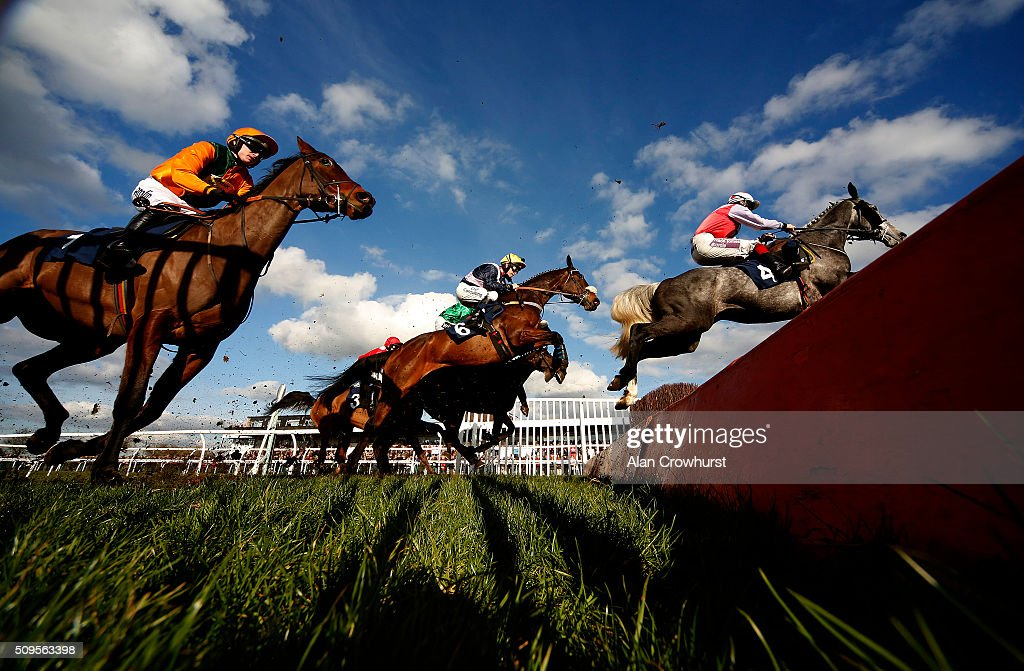Leighton Aspell riding Fight Commander (C, yellow cap) clear the open ditch on their way to winning The 32Red On The App Store Steeple Chase at Huntingdon racecourse on February 11, 2016 in Huntingdon, England.