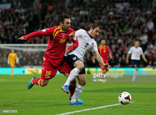 Leighton Baines of England battles with Nikola Drincic of Montenegro during the FIFA 2014 World Cup Qualifying Group H match between England and...