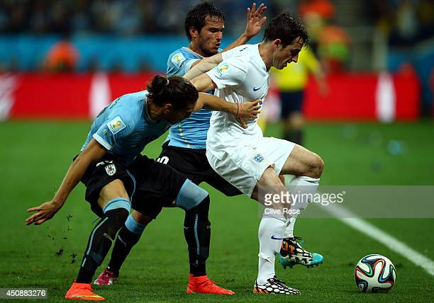 Leighton Baines of England fights off Martin Caceres and Alvaro Gonzalez of Uruguay during the 2014 FIFA World Cup Brazil Group D match between...
