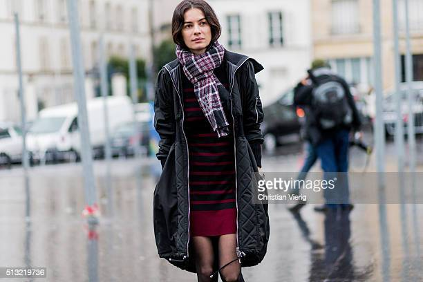 Leila Yavari is seen wearing a black coat and a red black striped dress outside Anthony Vaccarello during the Paris Fashion Week Womenswear...