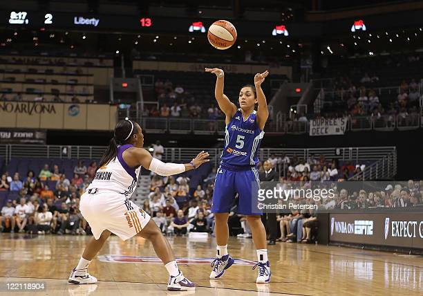 Leilani Mitchell of the New York Liberty passes the ball around Temeka Johnson of the Phoenix Mercury during the WNBA game at US Airways Center on...