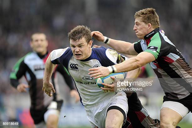 Leinster's centre Brian O'Driscoll gets tackled by Harlequins' wing David Strettle just short of the try line during the Heineken European Cup...