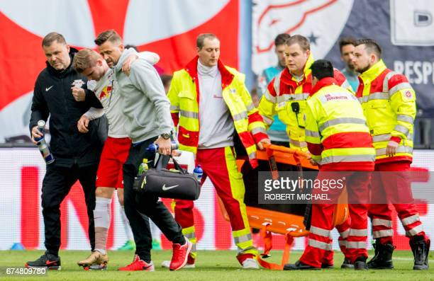 Leipzig's forward Timo Werner is helped as he leaves the pitch following injury during the German first division Bundesliga football match between RB...