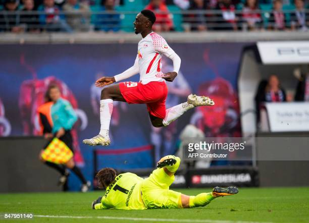 Leipzig´s French forward JeanKevon Augustin jumps over Moenchengladbach's Swiss goalkeeper Yann Sommer vie for the ball during the German first...