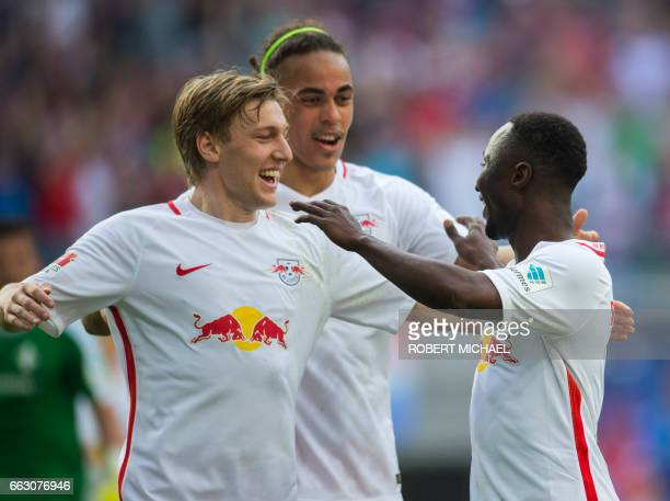 Leipzig's Guinean midfielder Naby Keita celebrates with his teammates Swedish forward Emil Forsberg and Danish forward Yussuf Poulsen after scoring...