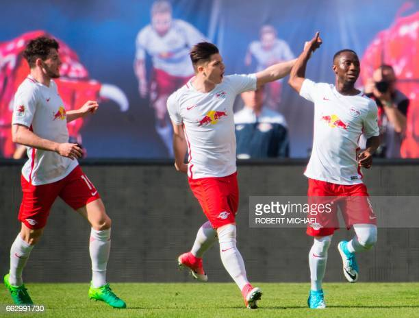 Leipzig's Guinean midfielder Naby Keita is congratulated by his teammates Scottish midfielder Oliver Burke and Austrian forward Marcel Sabitzer after...