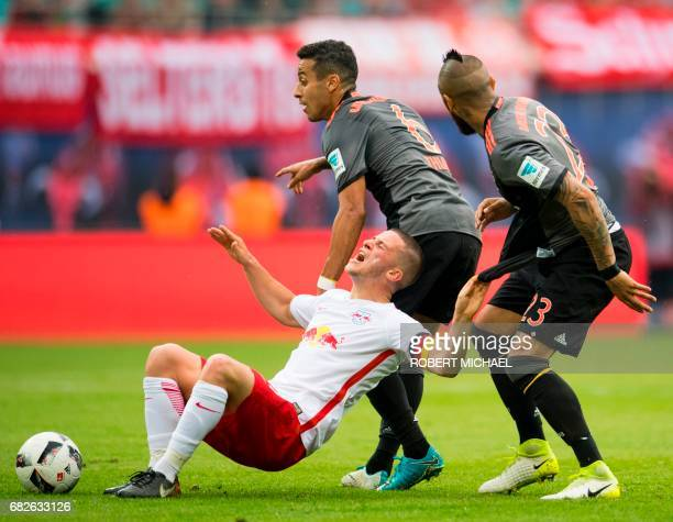 Leipzig's midfielder Diego Demme vies for the ball with Bayern Munich's Spanish midfielder Thiago Alcantara and Bayern Munich's Chilean midfielder...
