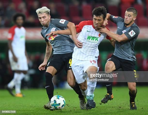 Leipzig's Slovanian midfielder Kevin Kampl Augsburg's South Korean midfielder Koo Jacheol and Leipzig's Swedish midfielder Emil Forsberg vie for the...