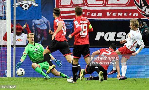 Leipzig's Swedish midfielder Emil Forsberg scores past MMainz' Danish goalkeeper Jonas Loessl during the German first division Bundesliga football...