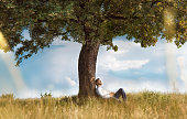 Human sitting under tree. Man repose on grass in nature. Outdoors - outside. No stress, carefree