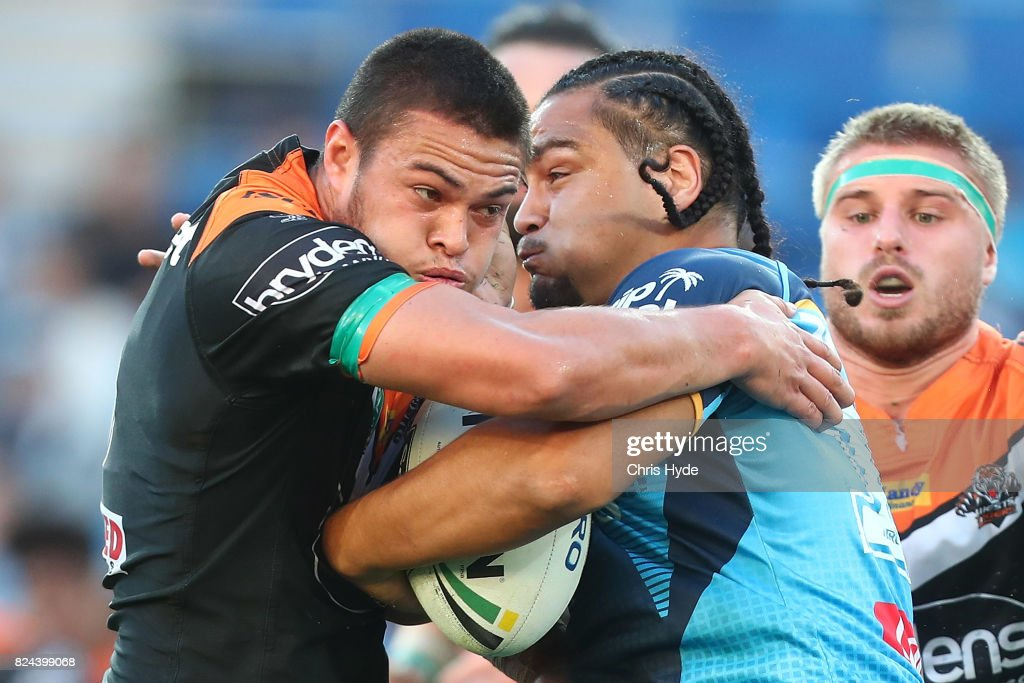 Leivaha Pulu of the Titans is tackled by Tuimoala Lolohea of the Tigers during the round 21 NRL match between the Gold Coast Titans and the Wests Tigers at Cbus Super Stadium on July 30, 2017 in Gold Coast, Australia.