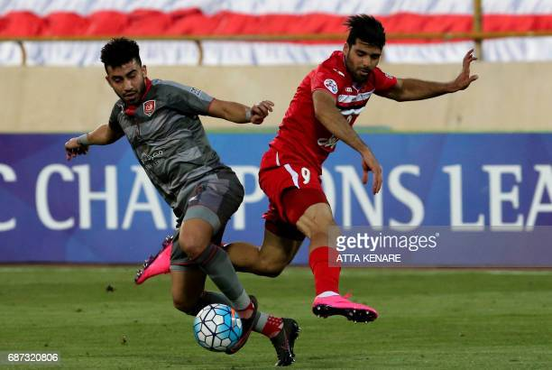 Lekhwiya's Ahmed Yasser fights for the ball against Persepolis' Mehdi Taremi during the Asian Champions League football match between Qatar's...
