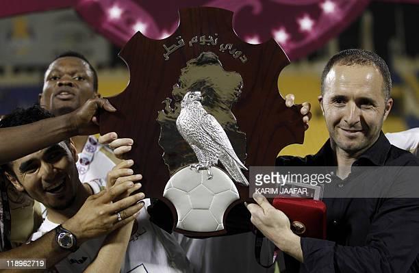 Lekhwiya's Algerian coach Djamel Belmadi holds the trophy with his team after Lekhwiya won the Qatari championship final football match against Umm...