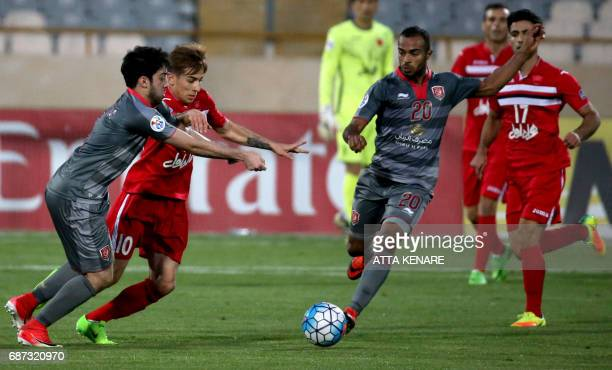 Lekhwiya's Ali Hassan kicks the ball as his teammate Khaled Muftah and Persepolis' Farshad Ahmadzadeh grapple during the Asian Champions League...