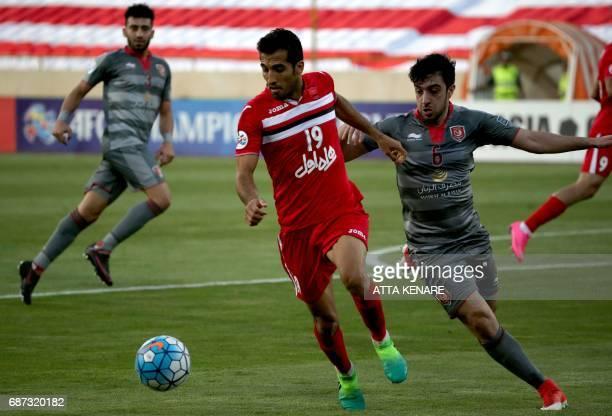 Lekhwiya's Khaled Muftah fights for the ball against Persepolis' Vahid Amiri during the Asian Champions League football match between Qatar's...