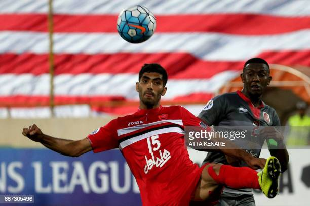 Lekhwiya's Mohamed Musa fights for the ball against Persepolis' Mohammad Ansari during the Asian Champions League football match between Qatar's...