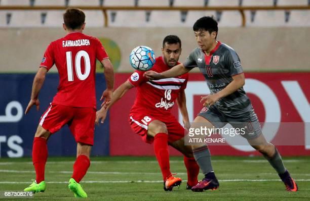 Lekhwiya's Nam Taehee fights for the ball against Persepolis' Mohsen Nodehi during the Asian Champions League football match between Qatar's Lekhwiya...