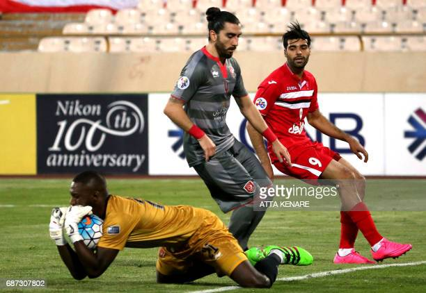 Lekhwiya's Qasem Abdullhamed saves the ball as his teammate Chico Flores and Persepolis' Mehdi Taremi look on during the Asian Champions League...