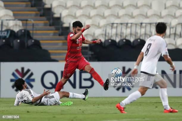 Lekhwiya's Qatar defender Ahmed Yasser evades a tackle by Jazira's Emirati midfielder Khalfan Mubarak during their AFC Champions League group B...