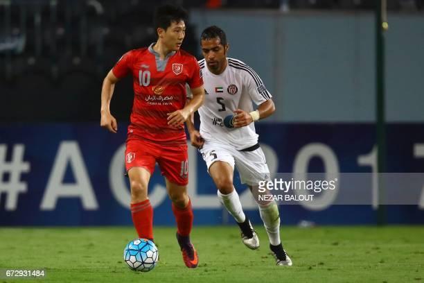 Lekhwiya's South Korean midfielder Nam Taehee dribbles past Jazira's Emirati defender Musallem Fayez during their AFC Champions League group B...