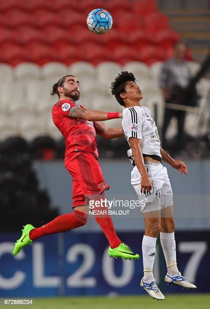 Lekhwiya's Spanish defender Chico Flores vies for the header with Jazira's Emirati forward Ahmed alAttas during their AFC Champions League group B...