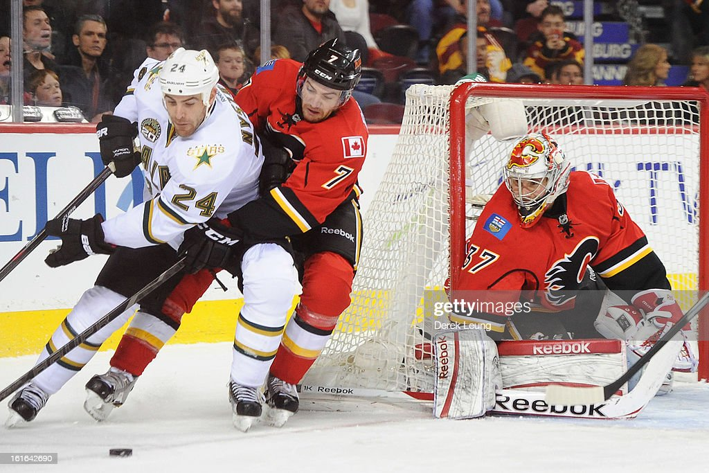 Leland Irving #37 of the Calgary Flames eyes the puck as his teammate T.J. Brodie #7 tries to check <a gi-track='captionPersonalityLinkClicked' href=/galleries/search?phrase=Eric+Nystrom&family=editorial&specificpeople=2209813 ng-click='$event.stopPropagation()'>Eric Nystrom</a> #24 of the Dallas Stars during an NHL game at Scotiabank Saddledome on February 13, 2013 in Calgary, Canada.