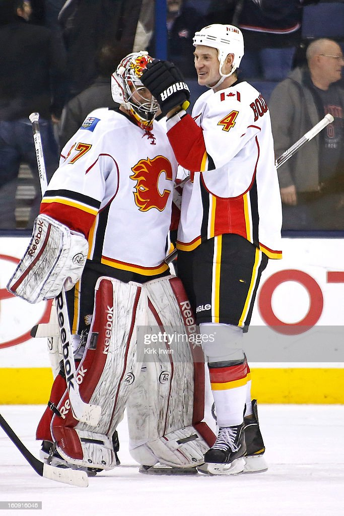 Leland Irving #37 of the Calgary Flames is congratulated by Jay Bouwmeester #4 of the Calgary Flames after getting his first NHL win after defeating the Columbus Blue Jackets 4-3 in overtime on February 7, 2013 at Nationwide Arena in Columbus, Ohio.