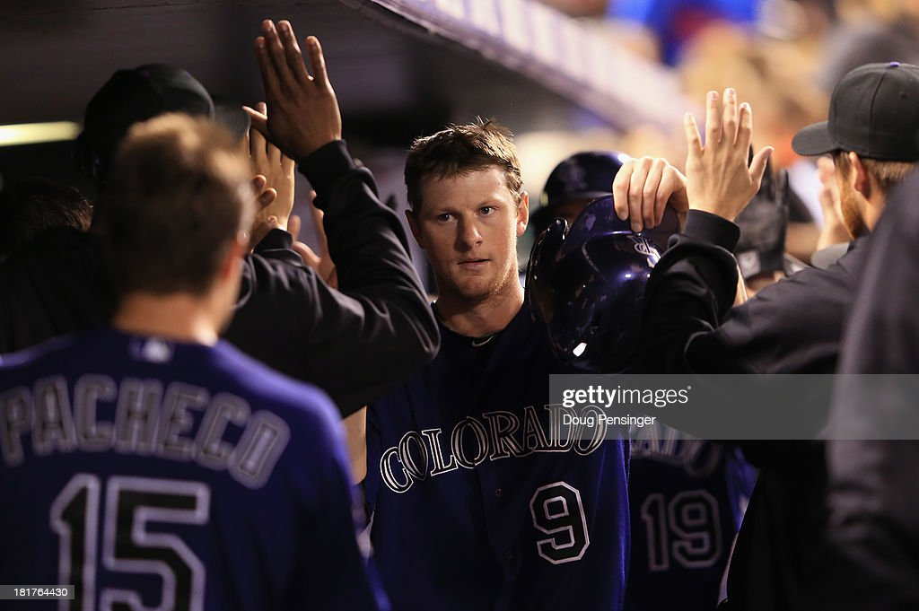 DJ LeMahieu #9 of the Colorado Rockies celebrates in the dugout after scoring on a two RBI single by Michael Cuddyer #3 of the Colorado Rockies off of Brandon Workman #67 of the Boston Red Sox in the seventh inning at Coors Field on September 24, 2013 in Denver, Colorado.