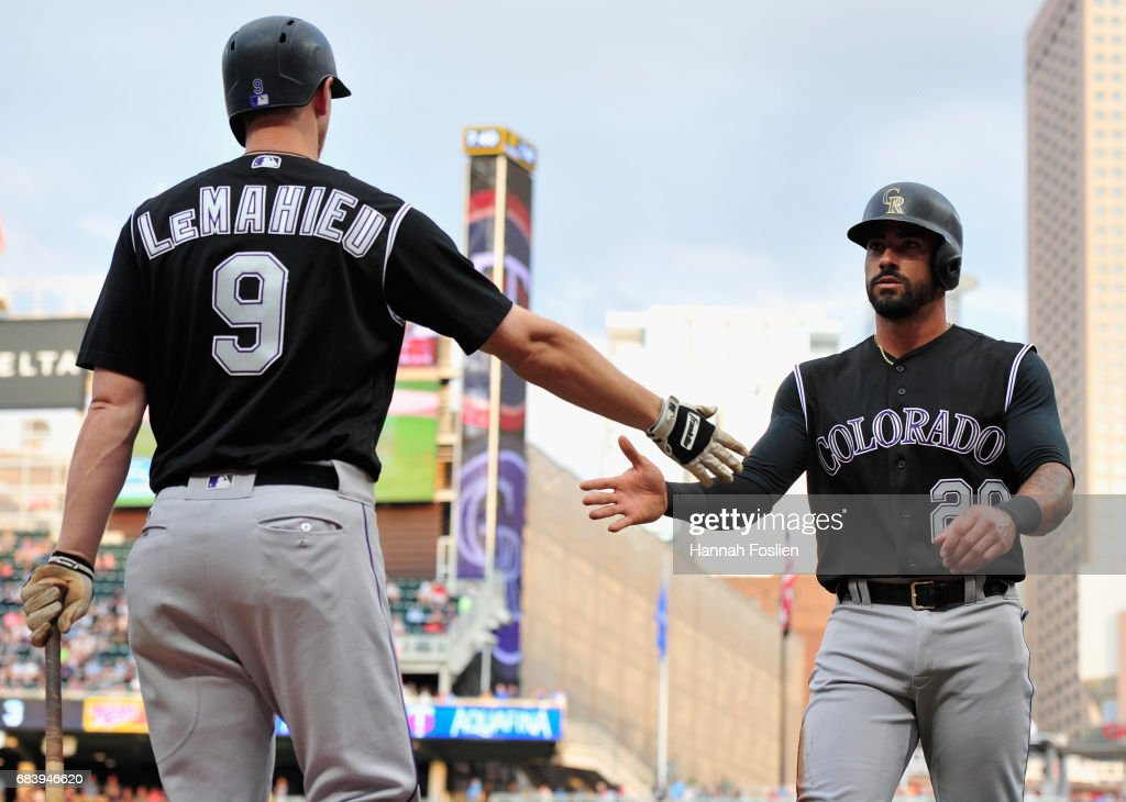 DJ LeMahieu #9 of the Colorado Rockies congratulates teammate Ian Desmond #20 on scoring a run against the Minnesota Twins during the second inning of the game on May 16, 2017 at Target Field in Minneapolis, Minnesota.