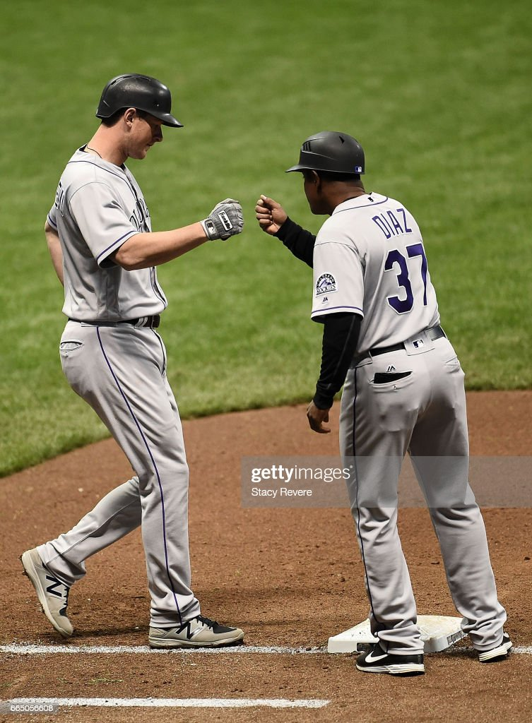 DJ LeMahieu #9 of the Colorado Rockies greets first base coach Tony Diaz #37 after drawing a walk during the sixth inning of a game against the Milwaukee Brewers at Miller Park on April 5, 2017 in Milwaukee, Wisconsin.