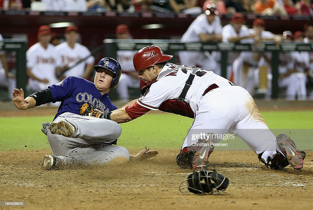 LeMahieu of the Colorado Rockies is tagged out at home plate by catcher Miguel Montero of the Arizona Diamondbacks as he attempts to score a run...