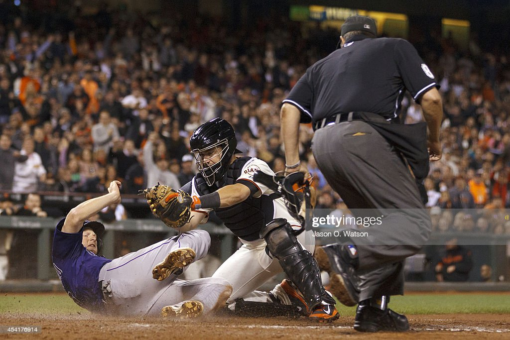 DJ LeMahieu #9 of the Colorado Rockies is tagged out by Andrew Susac #34 of the San Francisco Giants at home plate in front of umpire Doug Eddings #88 during the seventh inning at AT&T Park on August 25, 2014 in San Francisco, California.
