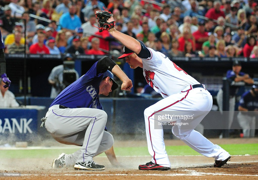 D. J. LeMahieu #9 of the Colorado Rockies scores on a wild pitch against <a gi-track='captionPersonalityLinkClicked' href=/galleries/search?phrase=David+Carpenter&family=editorial&specificpeople=1554475 ng-click='$event.stopPropagation()'>David Carpenter</a> #48 of the Atlanta Braves at Turner Field on July 29, 2013 in Atlanta, Georgia.