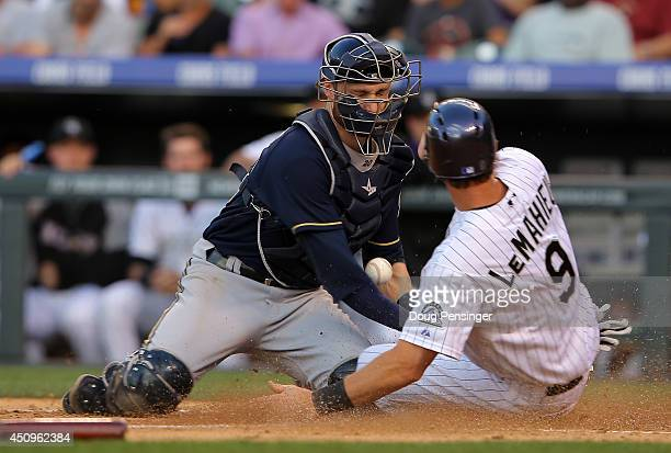 LeMahieu of the Colorado Rockies slides home to score on a single by Corey Dickerson of the Colorado Rockies as catcher Jonathan Lucroy of the...