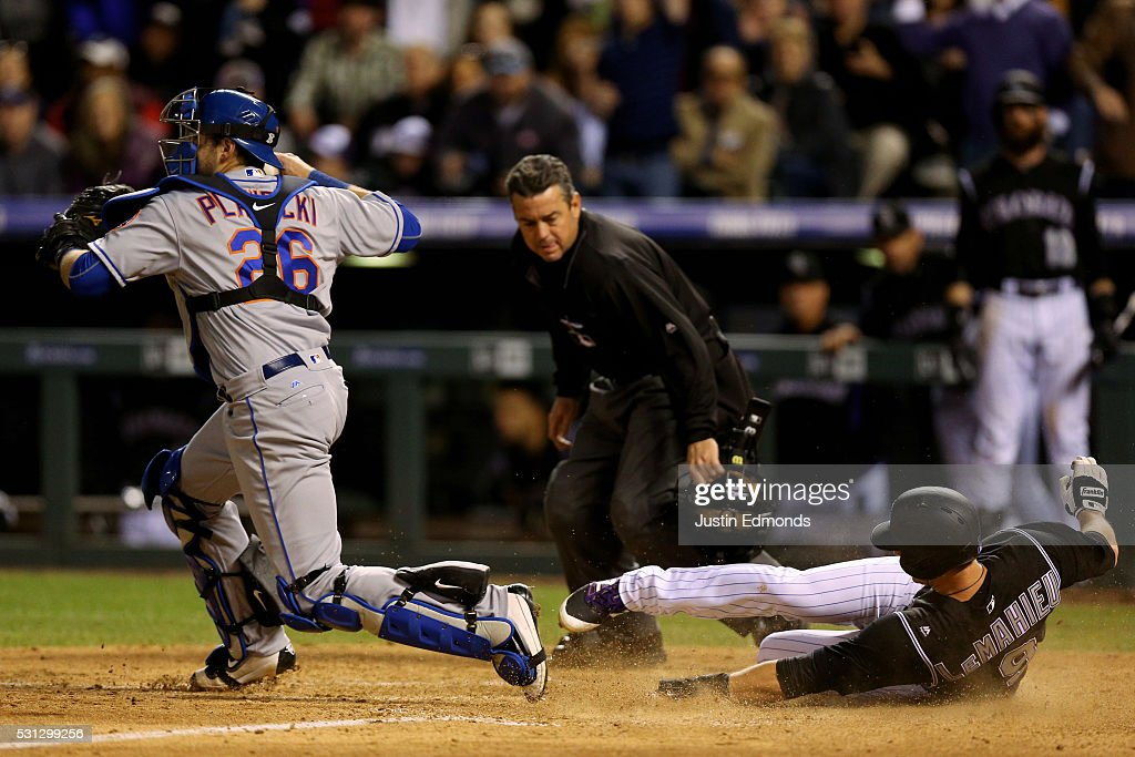 LeMahieu of the Colorado Rockies slides in to scores catcher Kevin Plawecki of the New York Mets decides to throw to second base instead of making a...