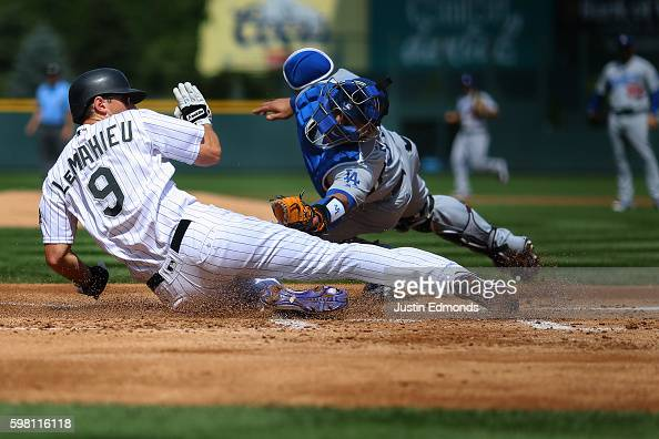 LeMahieu of the Colorado Rockies slides to score ahead of the tag from catcher Carlos Ruiz of the Los Angeles Dodgers on a double off the bat of...