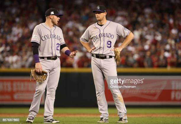 LeMahieu of the Colorado Rockies talks with Trevor Story during the bottom of the eighth inning of the National League Wild Card game against the...