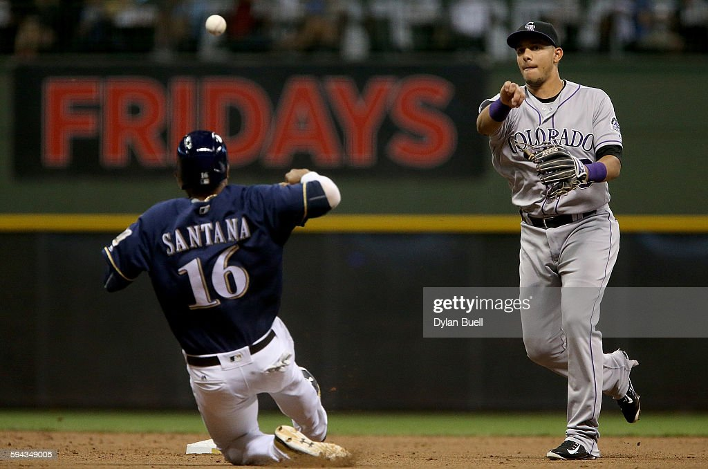DJ LeMahieu #9 of the Colorado Rockies turns a double play past Domingo Santana #16 of the Milwaukee Brewers in the sixth inning at Miller Park on August 22, 2016 in Milwaukee, Wisconsin.