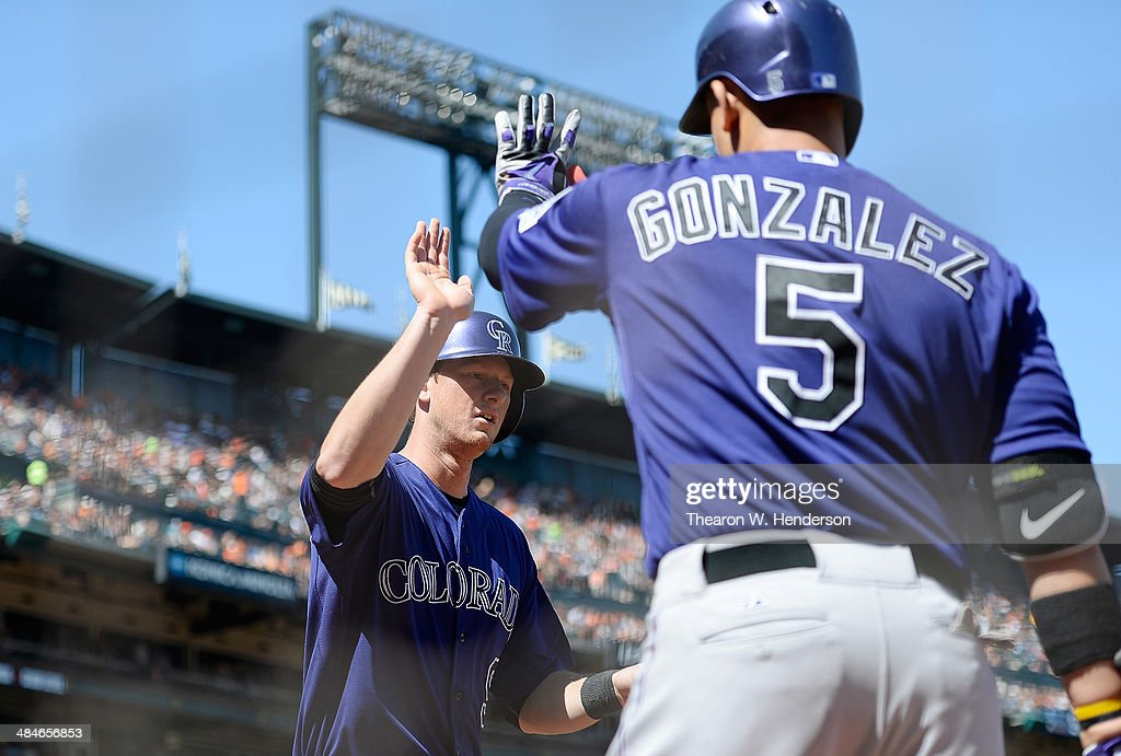 D.J. LeMahiew #9 of the Colorado Rockies is congratulated by Carlos Gonzalez #5 after scoring against the San Francisco Giants in the top of the eighth inning at AT&T Park on April 13, 2014 in San Francisco, California. LeMahiew scored on a pitch-hit RBI single from Drew Stubbs.
